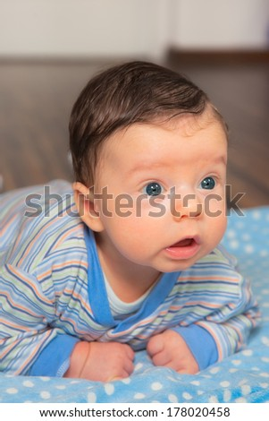Portrait of 2 months baby boy doing tummy time at home. - stock photo