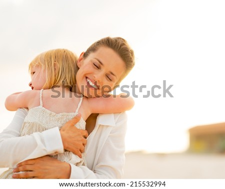 Portrait of mother and baby girl hugging on the beach in the evening - stock photo