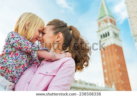 Portrait of mother and baby hugging against campanile di san marco in venice, italy - stock photo