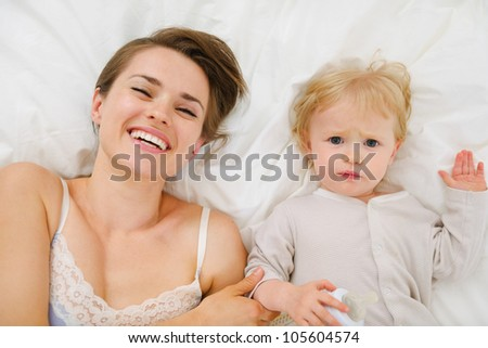 Portrait of mother and baby laying in bed. Upper view