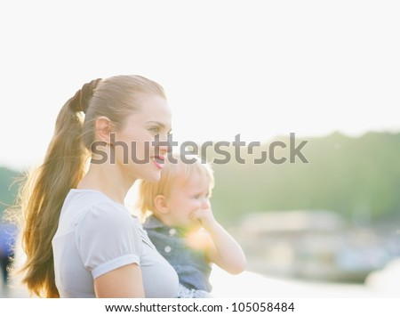 Portrait of mother and baby looking on copy space - stock photo