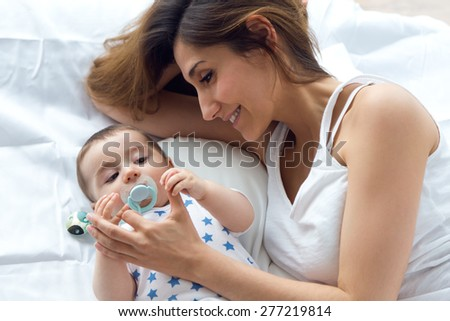 Portrait of mother and baby playing and smiling at home. - stock photo