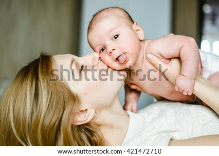 Portrait of mother and baby playing and smiling at home. Portrait of mother and baby playing and smiling at home. - stock photo