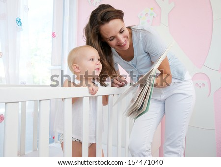 Portrait of mother and baby reading together from a book in bedroom