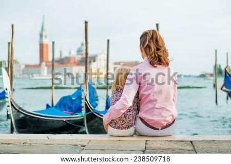 Portrait of mother and baby sitting on grand canal embankment in venice, italy. rear view - stock photo
