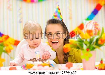 Portrait of mother and baby with birthday cake - stock photo