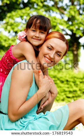 Portrait of mother and child sitting on the grass enjoying being together
