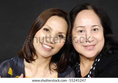 Portrait of mother and daughter both seniors in their 45s and 70s embracing - stock photo