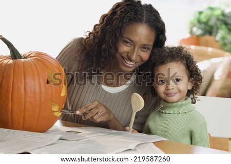Portrait of mother and daughter carving pumpkin - stock photo