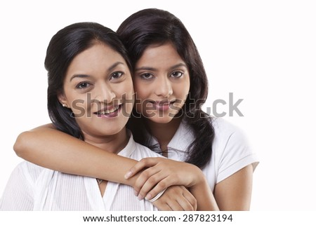 Portrait of mother and daughter embracing - stock photo