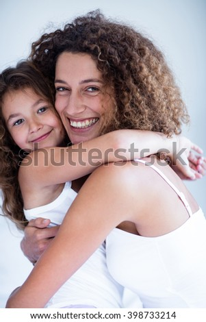Portrait of mother and daughter embracing at home - stock photo
