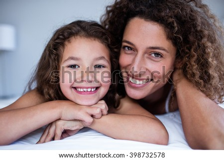 Portrait of mother and daughter embracing on bed in bedroom - stock photo