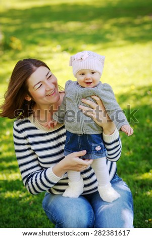 Portrait of mother and daughter, happy family of two, on the meadow in the park outside on a spring summer bright day, hugging, kissing and playing, mothers day concept holiday