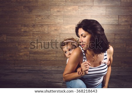 portrait of mother and daughter hiding behind her