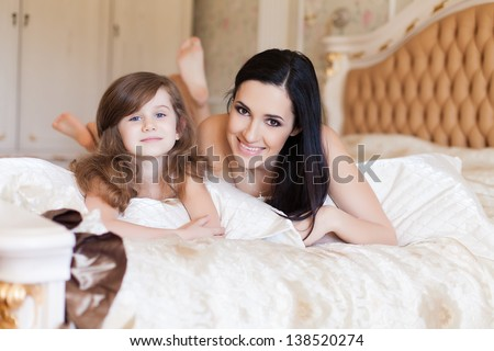 Portrait of mother and daughter in bed hugging and smiling. Morning