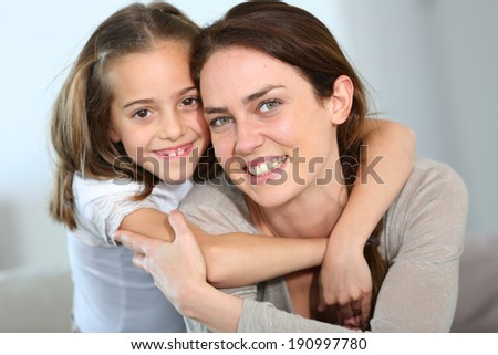 Portrait of mother and daughter in tender moment - stock photo