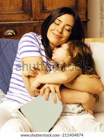 Portrait of mother and daughter lat home, happy family - stock photo