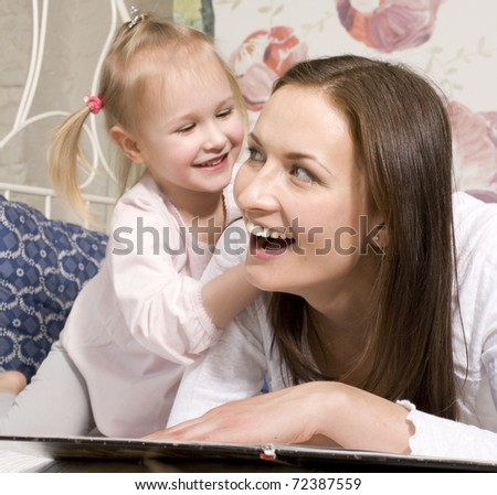 portrait of mother and daughter laying in bed  reading book and talking
