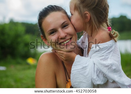 Portrait of mother and daughter outdoors forest river grass