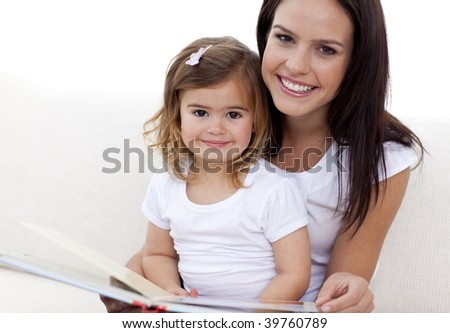 Portrait of mother and daughter reading a book in living-room