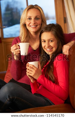Portrait Of Mother And Daughter Relaxing On Sofa Together With Hot Drink - stock photo