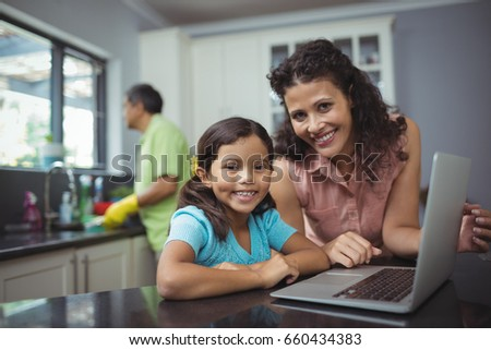 Portrait of mother and daughter using laptop in kitchen at home