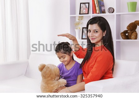 Portrait of mother and daughter with stuffed toy - stock photo