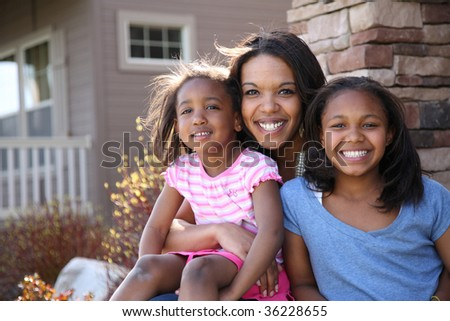 Portrait of mother and daughters sitting on porch - stock photo