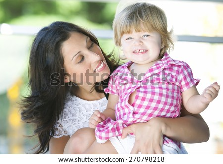 Portrait of mother and her beautiful blonde baby daughter - stock photo