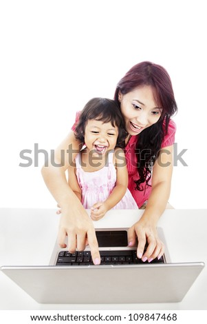 Portrait of mother and her daughter using laptop computer by pointing on the monitor - stock photo
