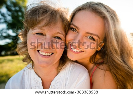 Portrait of mother and her teenage daughter outdoor in nature with setting sun in background - stock photo