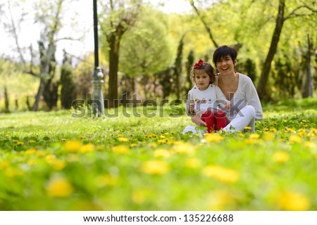 Portrait of mother and little girl playing in the park