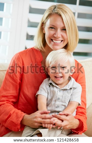 Portrait Of Mother And Son Sitting On Sofa At Home - stock photo