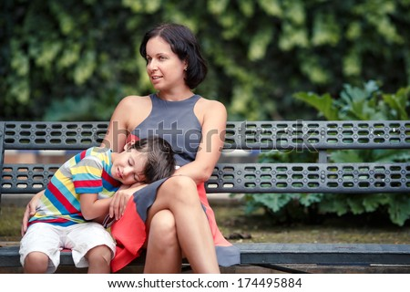 Portrait of mother and son sitting outdoors - stock photo