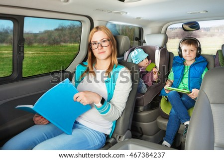 Portrait of mother and two sons sitting in the car