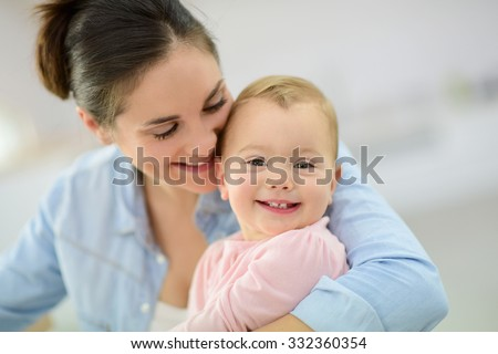 Portrait of mother cuddling her baby