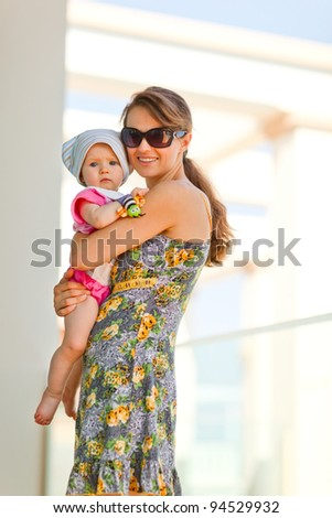 Portrait of mother holding baby on street - stock photo