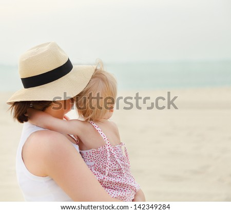Portrait of mother holding her bay girl at beach in summer - stock photo