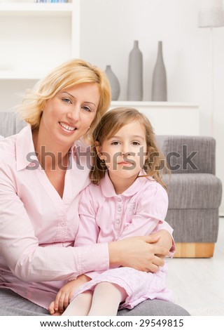Portrait of mother holding her daughter on knees, smiling.