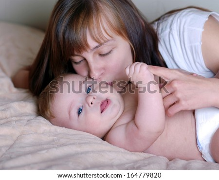 portrait of mother kissing her baby