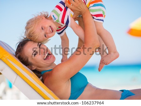Portrait of mother playing with baby on beach - stock photo