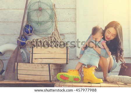 Portrait of mother playing with baby on beach .Mother and baby girl having fun time on beach in the evening.Vintage style. - stock photo