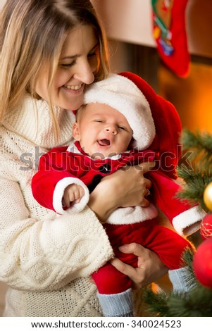 Portrait of mother posing with cute baby Santa