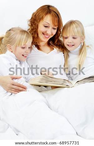 Portrait of mother reading the books to girls before dream