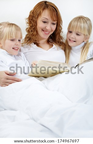 Portrait of mother reading to her daughters before sleep