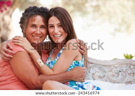 Portrait Of Mother With Adult Daughter On Garden Seat - stock photo