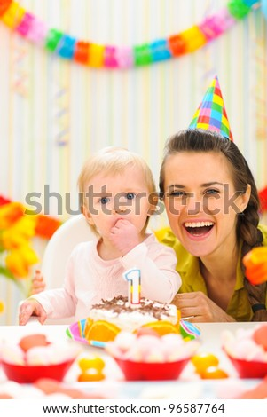Portrait of mother with baby enjoying first birthday cake