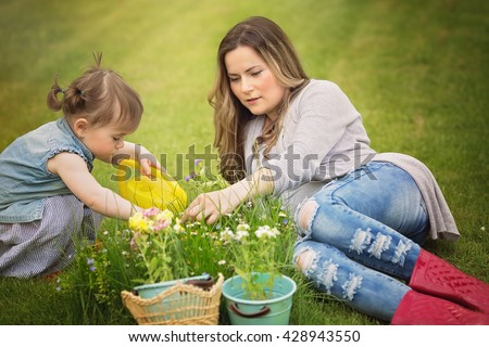 Portrait of mother with daughter planting flowers into the flowerpot in the garden - stock photo