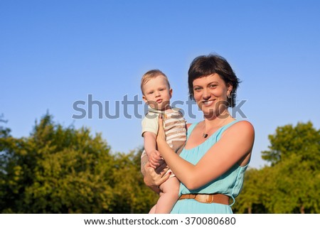 Portrait of Mother with Her Adorable Cute Sun Against Nature Background. Horizontal Image Orientation - stock photo