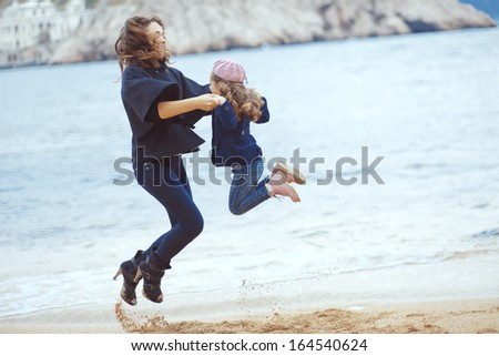 Portrait of mother with her daughter playing on berth near sea in the city, still life photo - stock photo